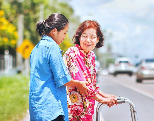 woman assisting the senior woman crossing the street